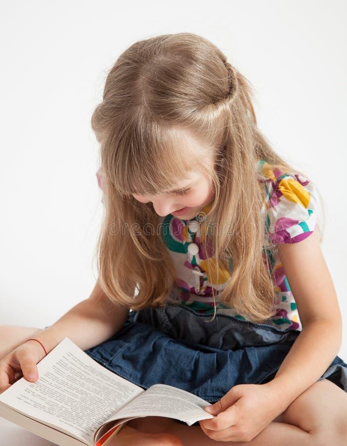 Le lilla flickan som läser en bok arkivfoto