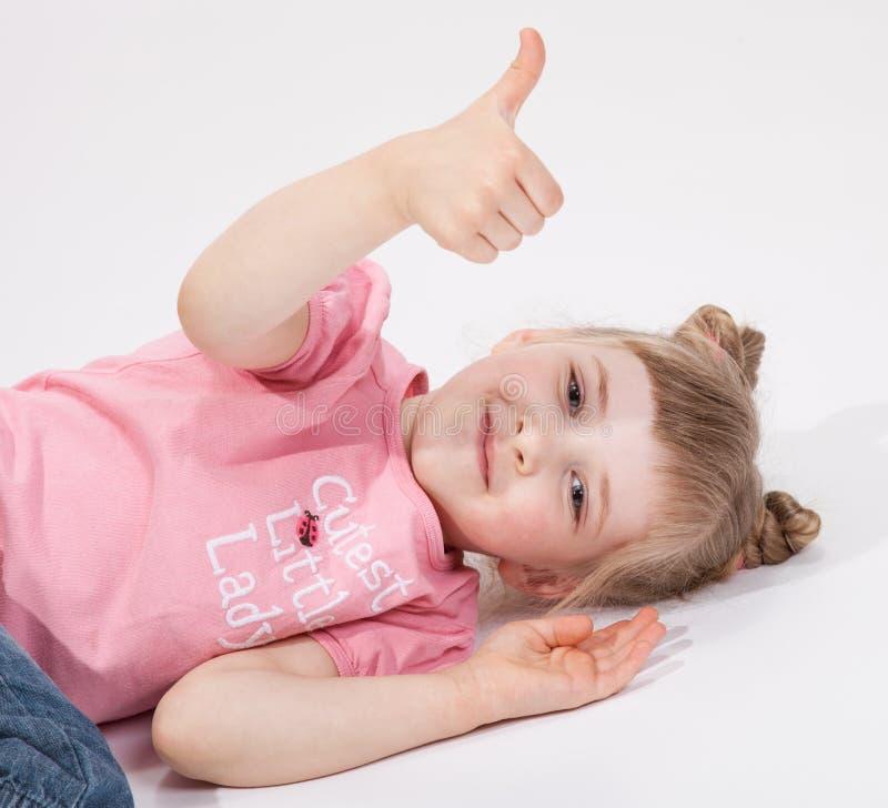 Le lilla flickan som ligger på golvet och visar upp tummen royaltyfria bilder