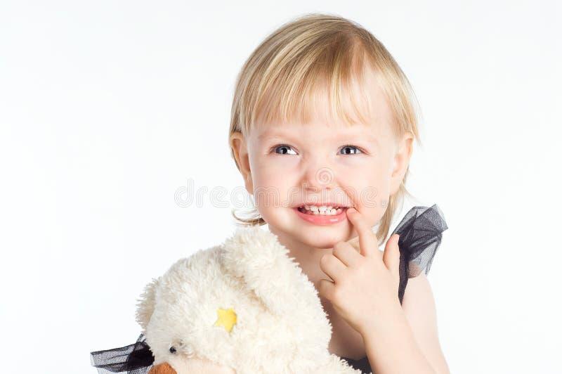 Le lilla flickan som pekar på hennes sunda vita tänder arkivfoton