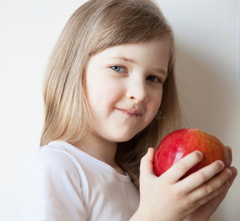 Le lilla flickan som rymmer ett äpple fotografering för bildbyråer