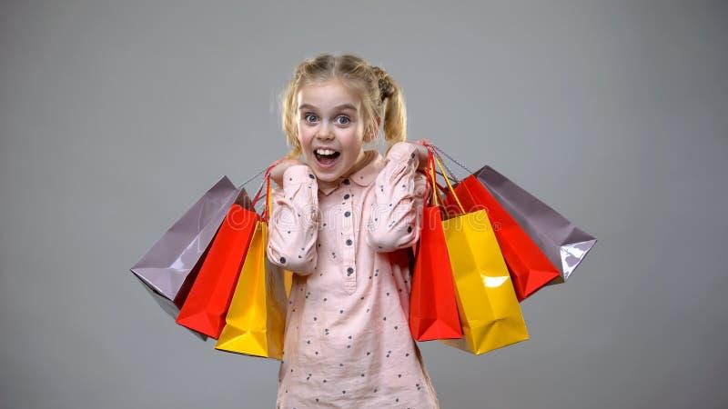 Le lilla flickan som rymmer färgrika köppåsar på grå bakgrund, rabatter royaltyfri fotografi