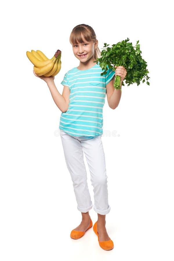 Le lilla flickan som rymmer nya persilja och bananer royaltyfria foton
