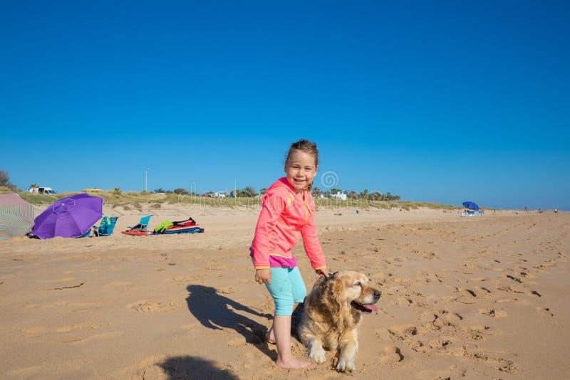 Le lilla flickan som ser med en hund på stranden royaltyfri foto