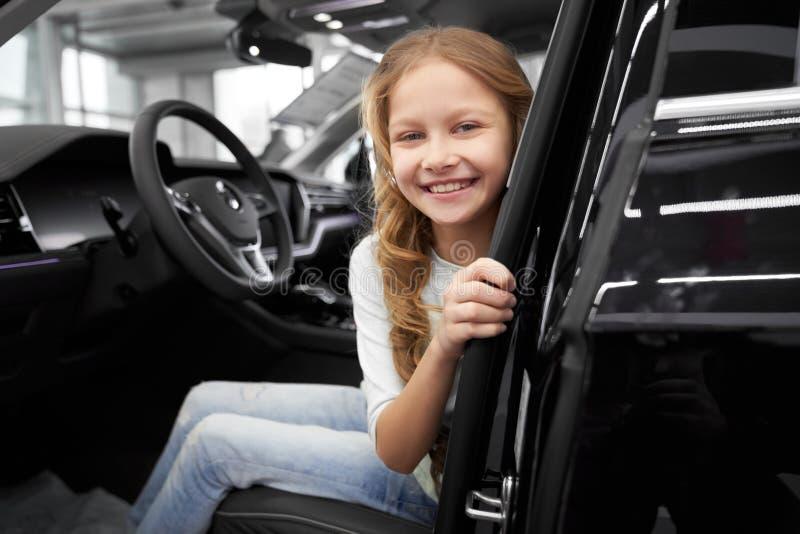 Le lilla flickan som sitter i förarsäte av den nya bilen arkivbild