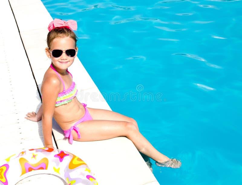 Le lilla flickan som sitter nära simbassäng royaltyfri fotografi