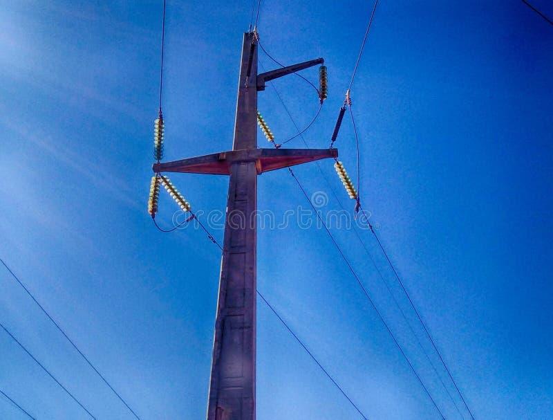 le linee della trasmissione filtra le linee elettriche, le torri e le linee elettriche lunghe in un campo di estate fotografia stock