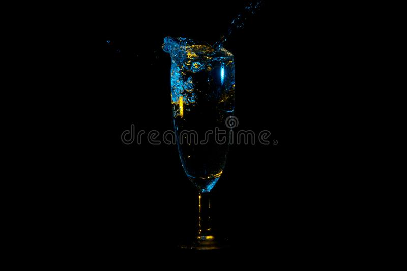 Le liquide bleu avec le jaune accentue l'éclaboussement hors d'un verre de vin d'isolement sur un fond noir photo stock