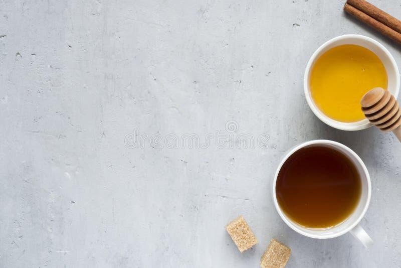 Le liquide de miel et une tasse de café avec du sucre allument le fond Copiez l'espace pour le texte images stock