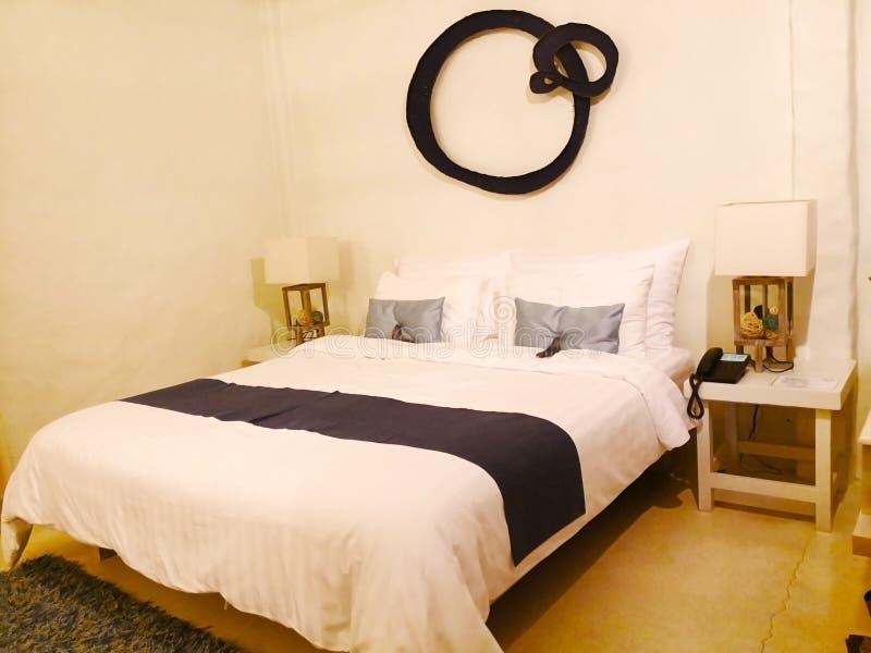 Le lit avec le tissu blanc Il y a peut des oreillers contre le wal photos libres de droits