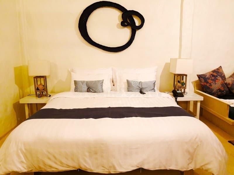 Le lit avec le tissu blanc Il y a peut des oreillers contre le wal photographie stock