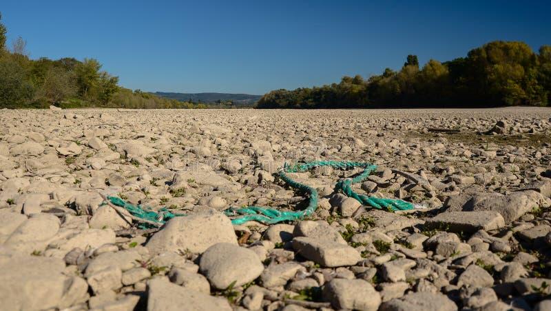 Le lit de la rivière sec un beau jour d'automne avec les arbres évidents et la turquoise cassée rope photos libres de droits