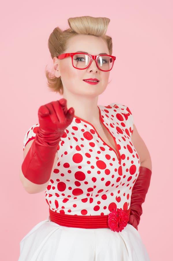 Le livlig blond kvinnlig som pekar på kameran i röda handskar och exponeringsglas på rosa rosa bakgrund royaltyfri bild