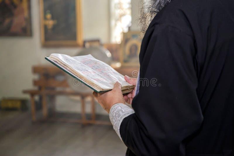 Le livre avec des prières dans les mains d'un prêtre orthodoxe image stock