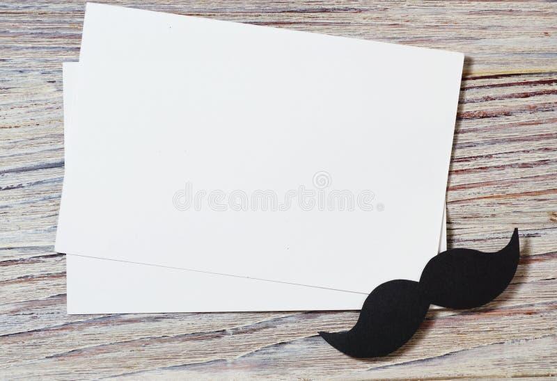 Le livre blanc enveloppent sur la vieille table en bois avec le ton de cru Moustache de papier noire Le jour de père heureux - mo photos stock
