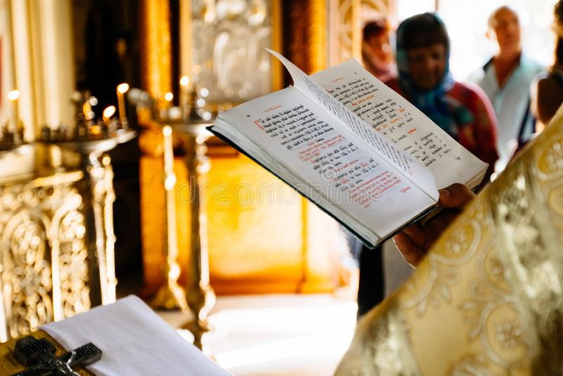 Le livre chrétien d'église de lecture de prêtre, prêtre lit une prière au-dessus de la bible photos libres de droits