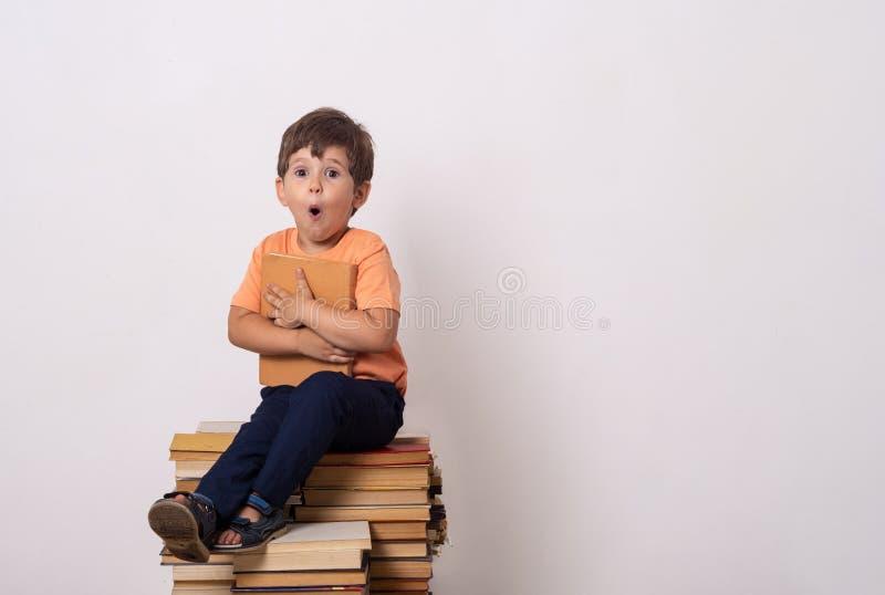Le livre de lecture de petit enfant et dans des couvertures de confusion disent du bout des lèvres Enfant avec des verres se repo images libres de droits