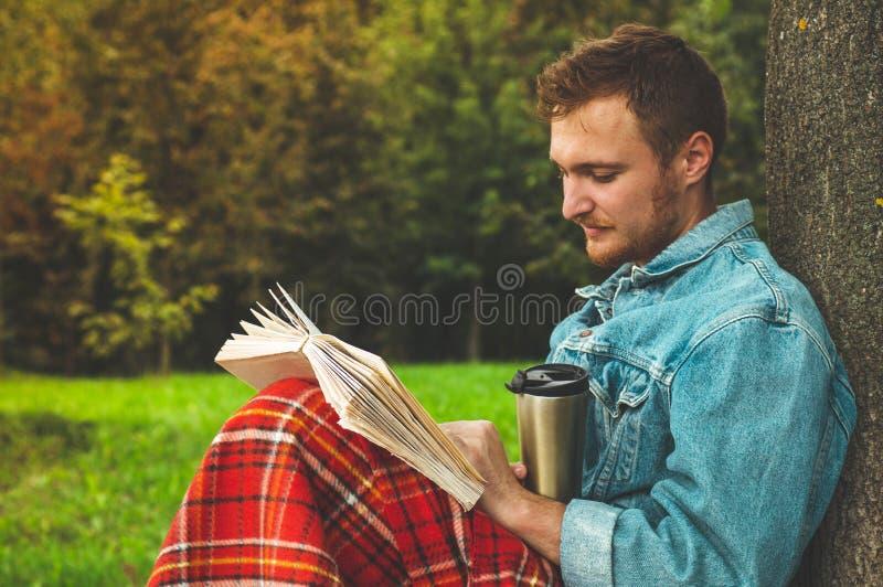 Le livre de lecture de sourire de jeune homme extérieur avec un plaid rouge chaud et une tasse de thé l'automne de fond vacations photographie stock libre de droits