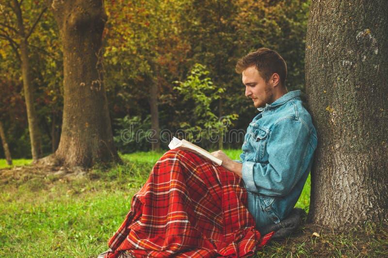 Le livre de lecture de sourire de jeune homme extérieur avec un plaid rouge chaud et une tasse de thé l'automne de fond vacations images stock