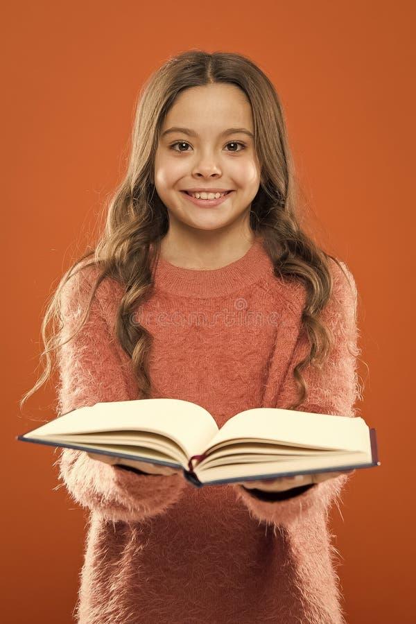 Le livre de prise de fille a lu l'histoire au-dessus du fond orange L'enfant appr?cient le livre de lecture Concept de librairie  photos stock