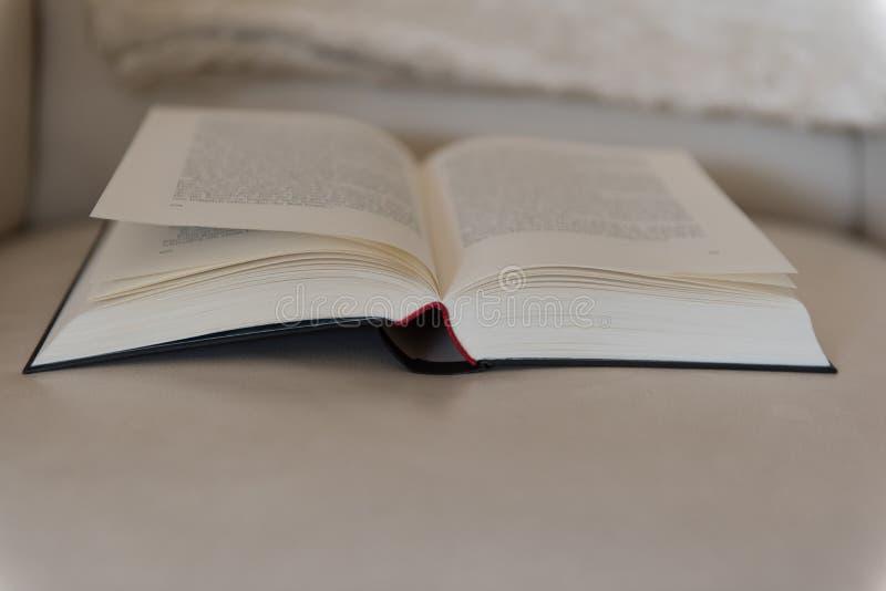 Le livre ouvert se trouve sur une chaise en cuir image stock