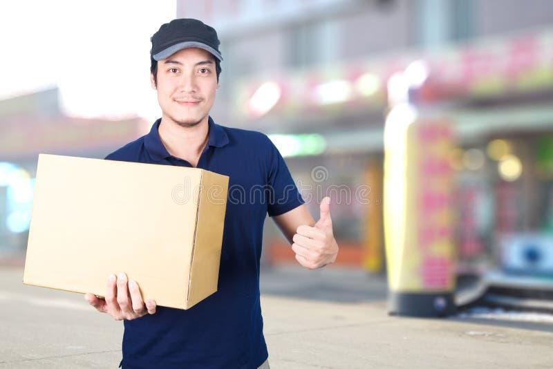 Le livreur asiatique manie maladroitement avec la boîte en carton sur le backg brouillé images stock