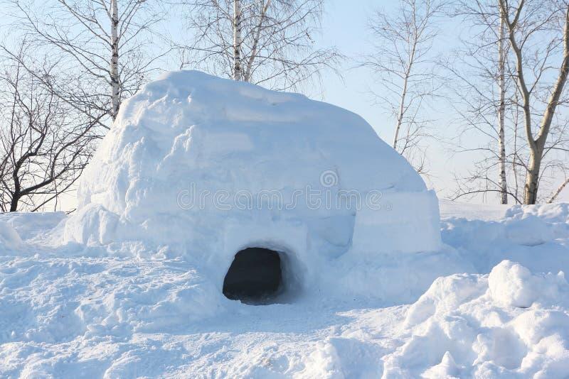 Le logement un igloo sur une clairière de neige pendant l'hiver au coucher du soleil images libres de droits