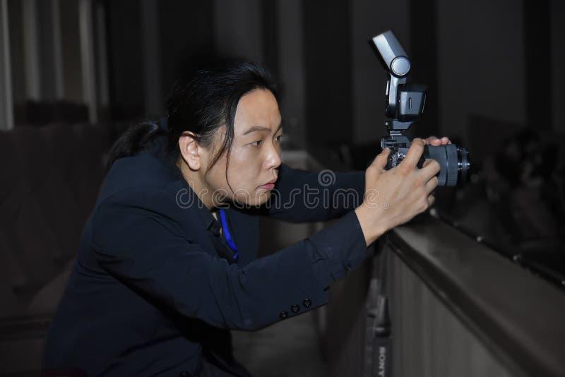Le long photographe asiatique de cheveux dans le costume de marine s'est concentré avec le sien images libres de droits