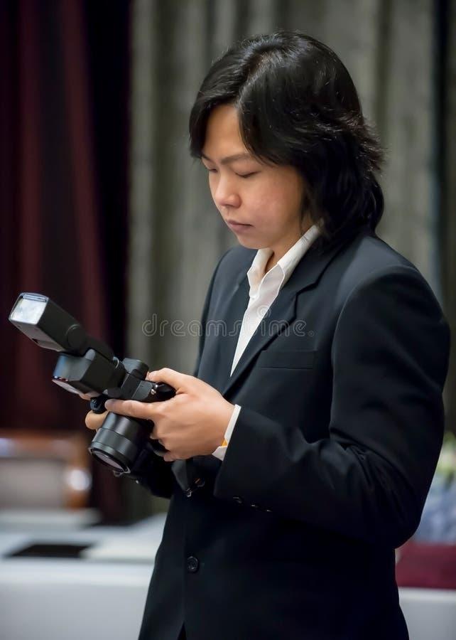 Le long photographe asiatique de cheveux dans le costume de marine s'est concentré avec le sien images stock