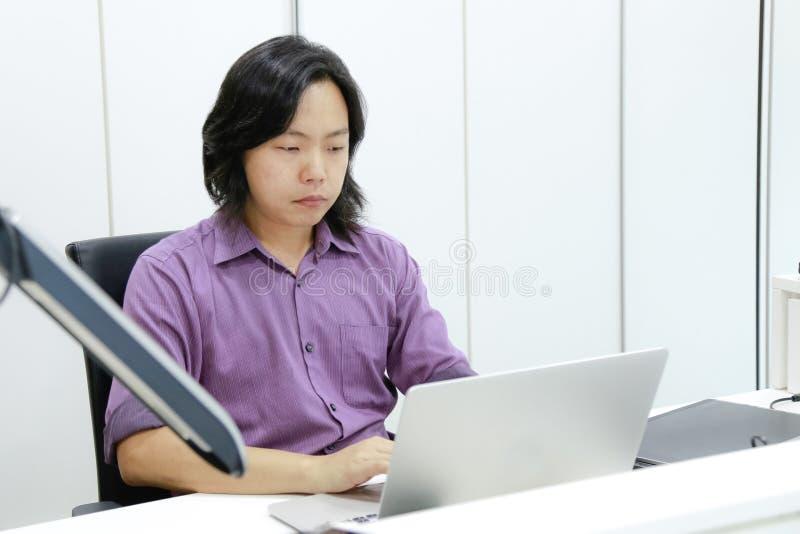 Le long type asiatique de cheveux se concentre et se concentre sur son travail dans le fron photo stock