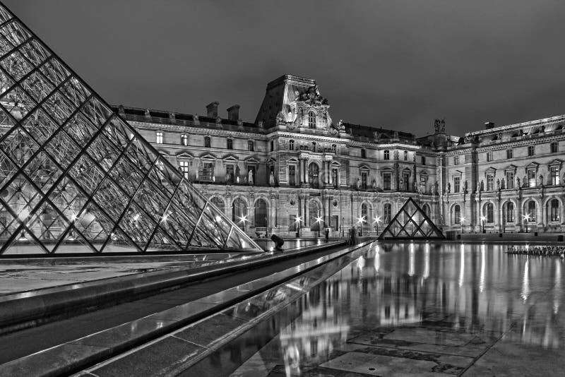 Le Louvre et les pyramides ont longtemps exposé la photo noire et blanche de nuit photographie stock libre de droits