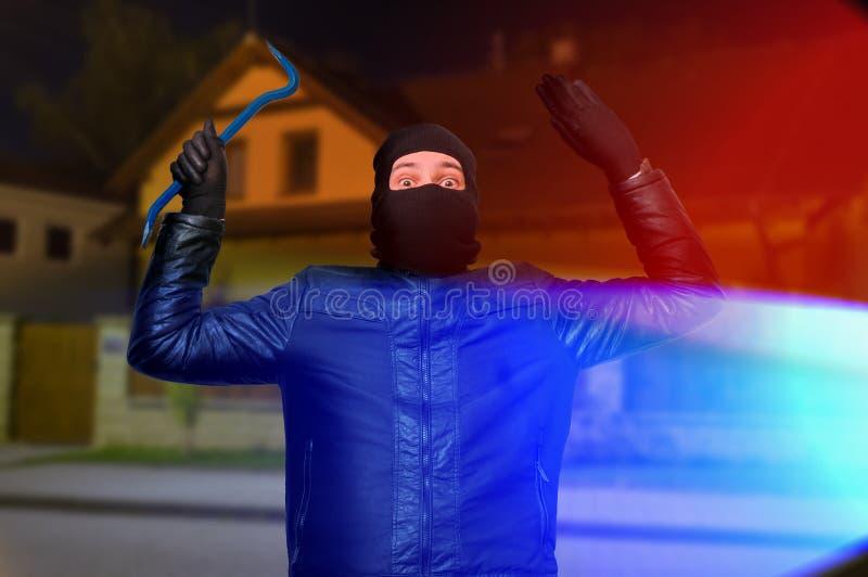 Le luci della polizia e lo scassinatore o il ladro mascherato con la passamontagna è arre fotografie stock