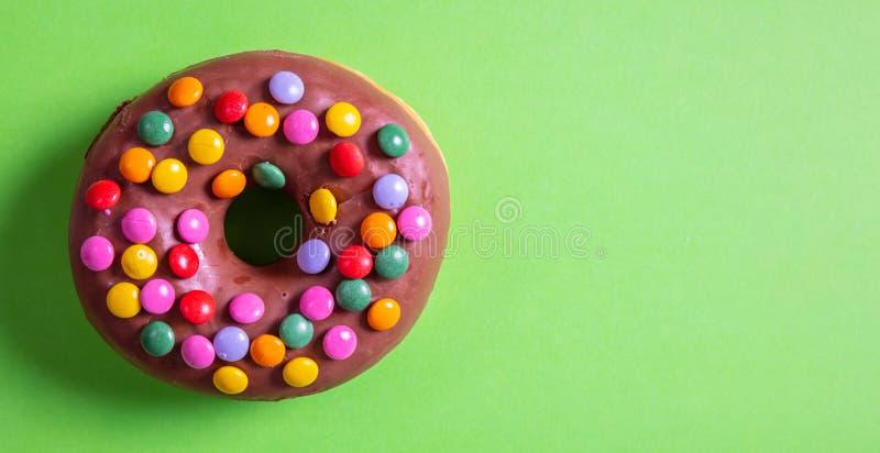 Le lustre de chocolat de beignet et arrose, vue supérieure et d'isolement avec l'espace de copie, sur le fond vert image stock