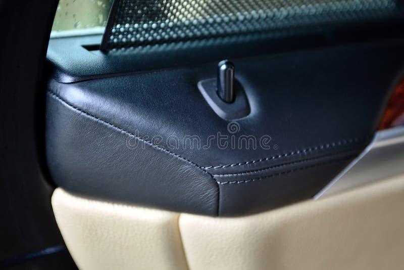 Le luxe en gros plan a piqué l'intérieur exclusif en cuir dans des couleurs noires et beiges d'une voiture de luxe avec un bouton photographie stock