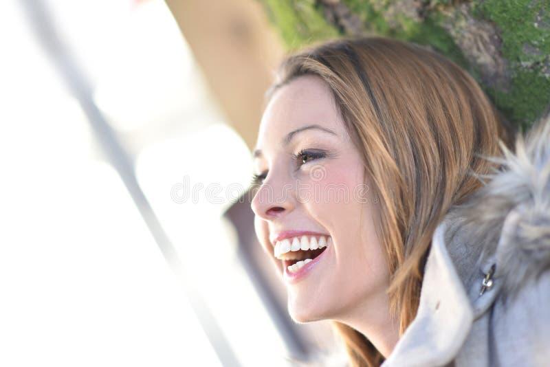 Le lycklig kvinnabenägenhet på träd fotografering för bildbyråer
