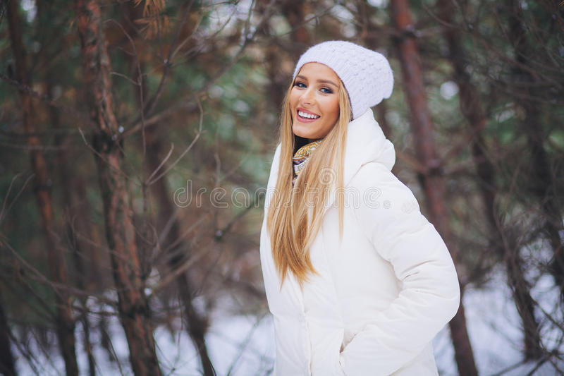 Le lycklig ung flicka som går i vinterskog royaltyfri foto