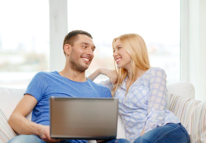 Le lyckliga par med den hemmastadda bärbara datorn arkivbild