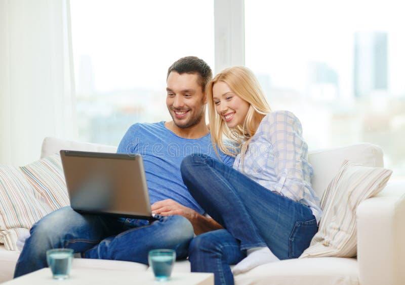Le lyckliga par med den hemmastadda bärbara datorn royaltyfria bilder