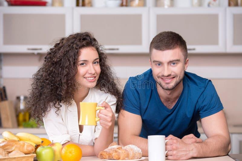 Le lyckliga par som in dricker morgonkaffe royaltyfri bild