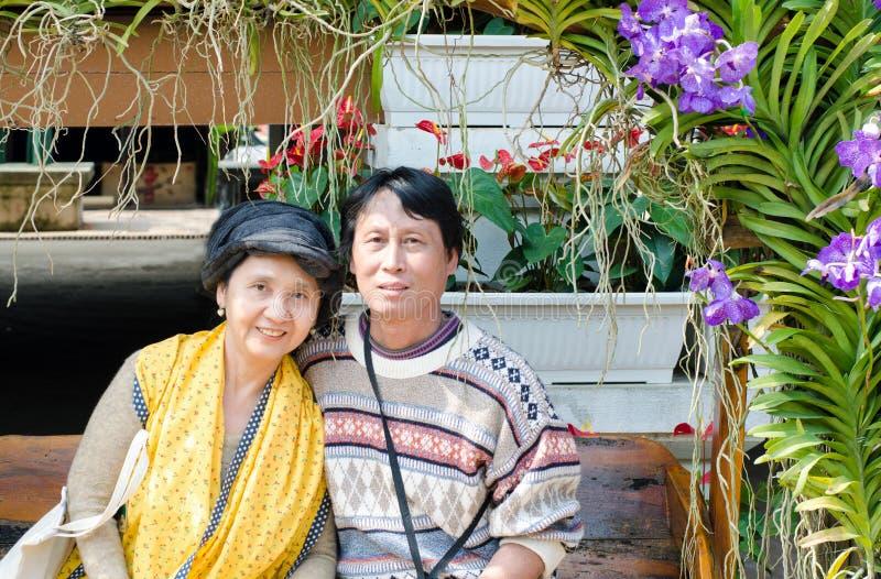 Le lyckliga pensionärpar i trädgård royaltyfria bilder