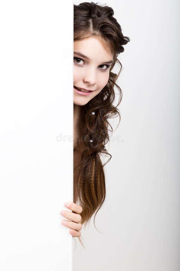 Le lyckligt anseende för ung kvinna bak och luta på en vitt tomt affischtavla eller plakat, uttrycker olikt royaltyfria bilder