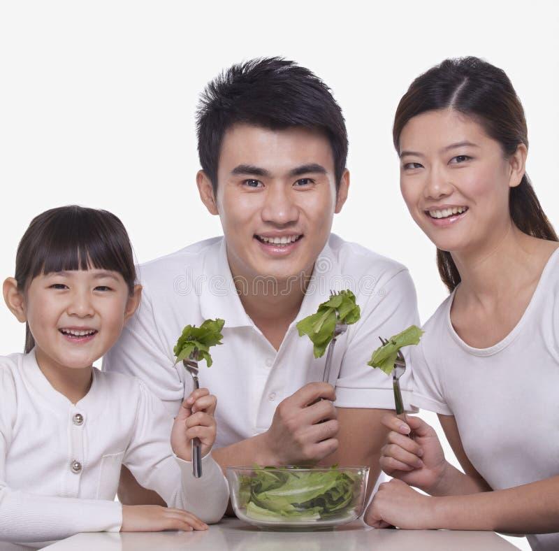 Le lyckligt familjsammanträde på tabellen som delar en sallad ut ur en bunke, studioskott royaltyfria foton