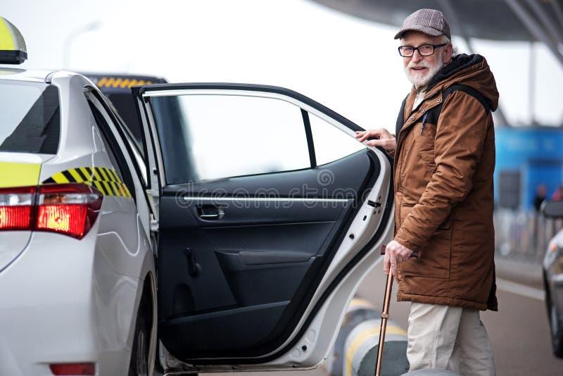 Le mâle âgé gai est automobile proche debout photographie stock libre de droits
