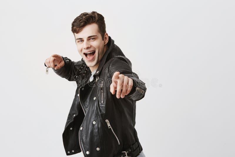 Le mâle élégant utilise la veste en cuir noire au-dessus du T-shirt gris, souriant largement, points à l'appareil-photo avec les  photo libre de droits