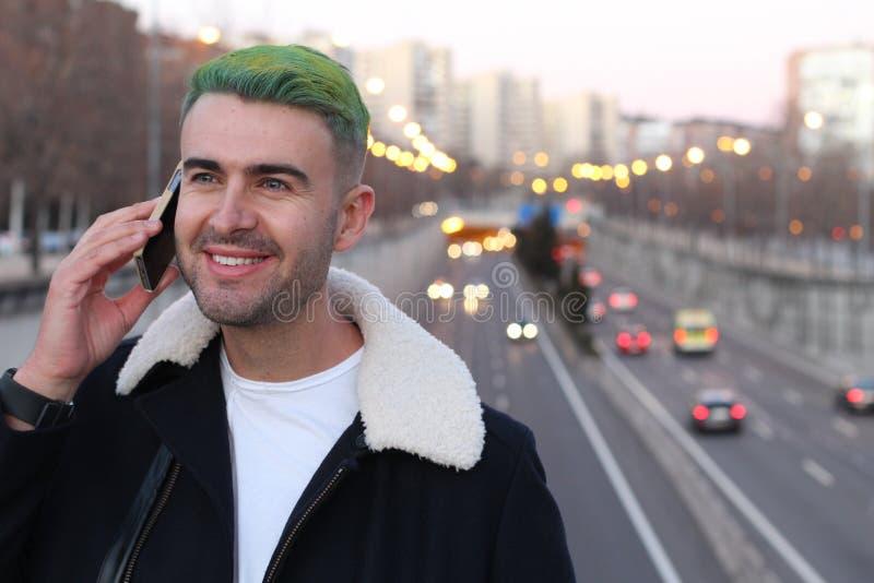 Le mâle énervé avec le vert a teint des cheveux appelant par le téléphone photos libres de droits