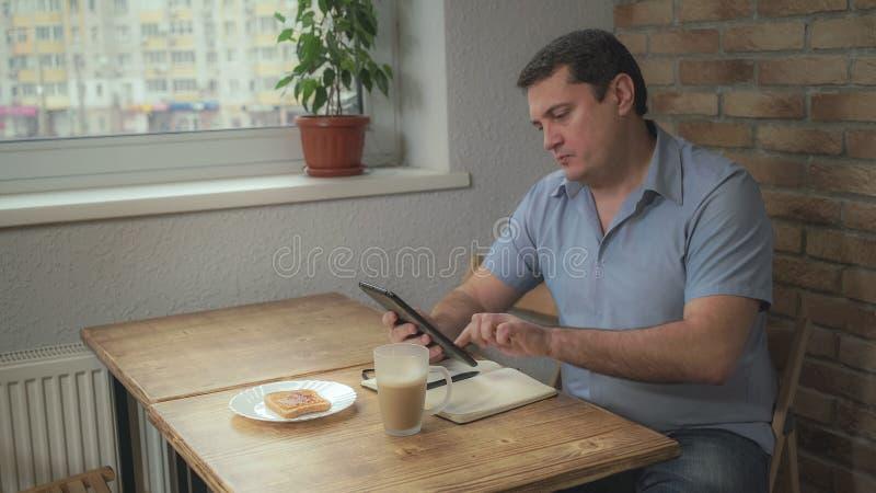 Le mâle adulte pendant le matin au café d'hôtel et au pain grillé potables de consommation, est sur la table et le comprimé quoti images stock