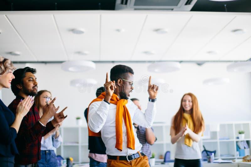 Le mâle africain danse avec les doigts augmentés tandis que ses amis battent des mains photographie stock