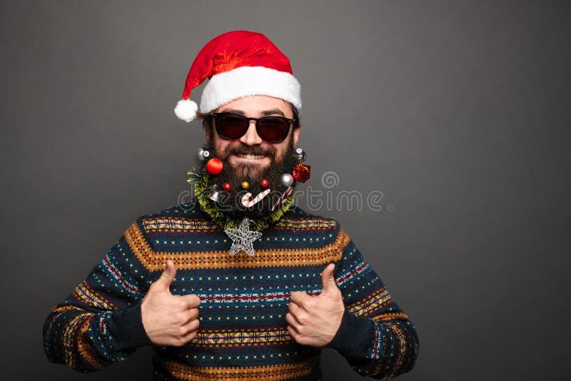 Le mâle barbu dans le chapeau de Santa montre des pouces  image libre de droits