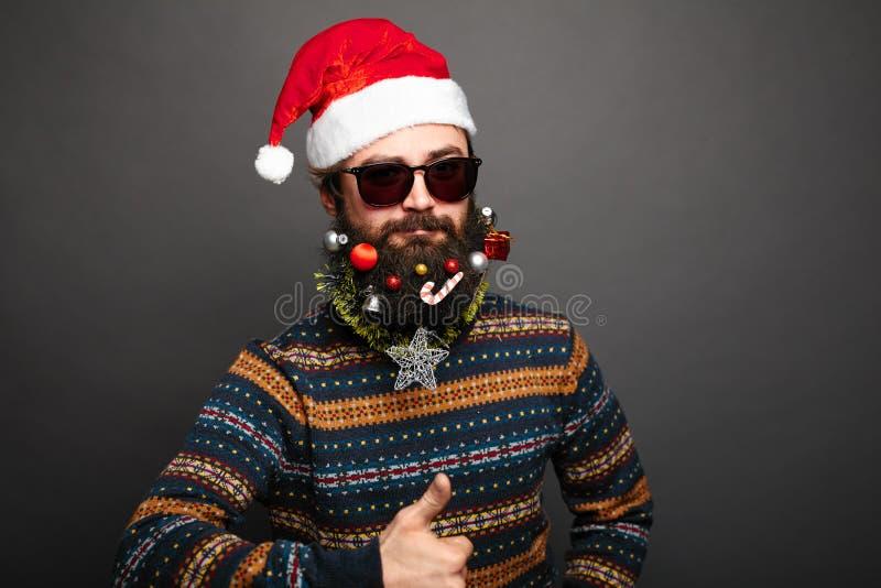 Le mâle barbu dans le chapeau de Santa montre des pouces  images stock