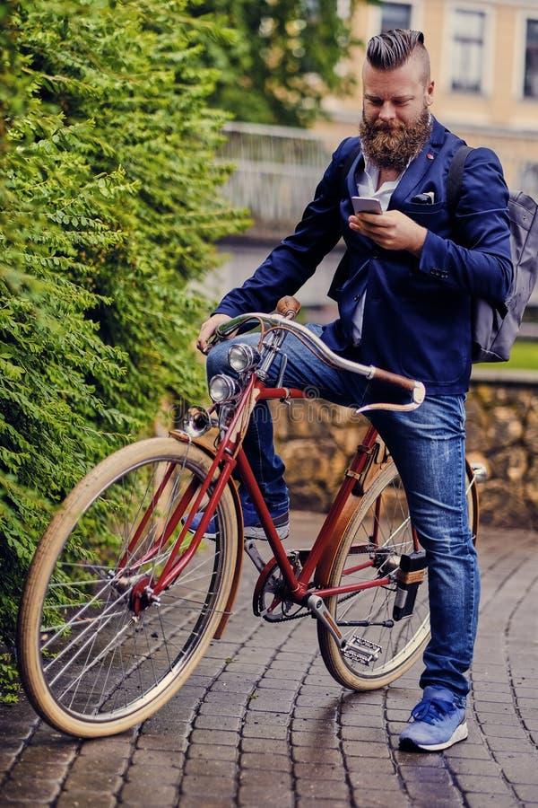 Le mâle barbu en parc parle par le téléphone intelligent photos libres de droits