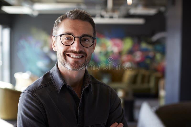 Le mâle blanc âgé moyen créatif dans le secteur occasionnel de salon de bureau regarde à la caméra souriant, fin  photos libres de droits